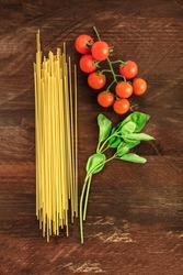 An overhead photo of a letter P for pasta, formed by spaghetti, cherry tomatoes, and a sprig of basil leaves, on a dark wooden background texture with copy space