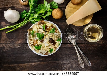 Shutterstock An overhead photo of a mushroom risotto, with champignons, fresh parsley, porcini, a slice of Parmesan, a glass of white wine, a fork and a spoon, and a place for text, on a dark rustic texture