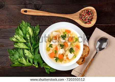 An overhead photo of a plate of chicken and noodles soup, shot from above on a dark rustic texture with a spoon, a wooden ladle with peppercorns, slices of bread, a celery branch, and a place for text