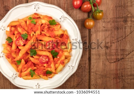 Stock Photo An overhead photo of a plate of pasta with tomato sauce. Penne rigate with cherry tomatoes and fresh parsley leaves, on a dark rustic texture with a place for text
