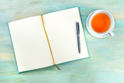 An overhead photo of an open journal notebook with a pen and a cup of tea, shot from above, a diary on a teal blue background with a place for text
