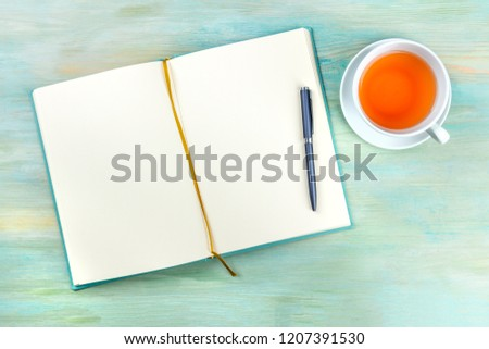 An overhead photo of an open journal notebook with a pen and a cup of tea, shot from above, a diary on a teal blue background with a place for text ストックフォト ©