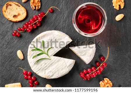 An overhead photo of Camembert cheese with a glass of red wine, fruits and nuts, shot from above on a black background