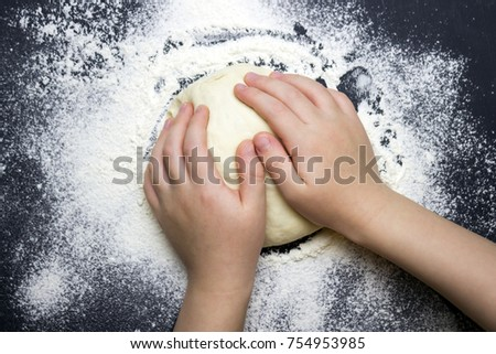 An overhead photo of kid's hands, some sprinkled flour and wheat dough on the black table with a place for text. Child's hands making the dough for backing bread. Little child cooking dough or pastry #754953985