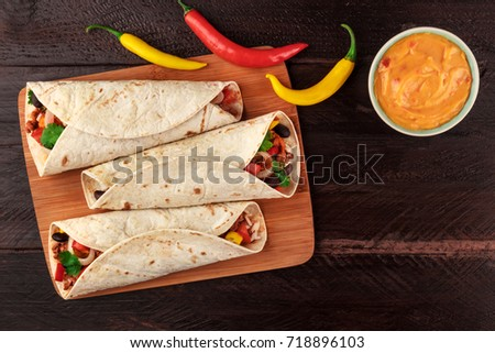An overhead photo of Mexican burritos with beef, rice, black beans, and vegetables, with a cheese sauce, chili peppers, and a place for text, shot from above on dark wooden rustic textures