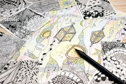 An overhead photo of the abstract hand drawn doodle patterns made of black liner pen. Pen strokes. Doodle, tangle illustration. Zen art, sketch illustration. Lesson for artist, painters