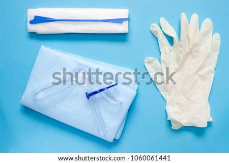 An overhead photo of the vaginal speculum, napkin, medicine gloves and spatula. The medical tools for holding open the vagina during medical investigation. Feminine woman health diagnosis