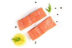 An overhead photo of two slices of salmon on a white background with a place for text, with slices of lemon, salt and pepper, and dill sprigs
