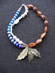 An overhead vertical shot of a neckless with leaves on a black surface