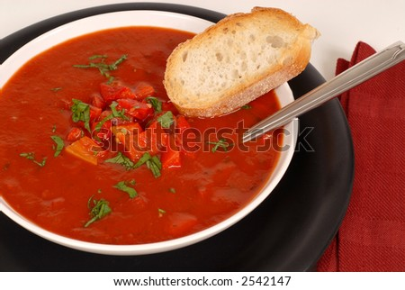 An overhead view of a bowl of tomato, red pepper and basil soup with bread