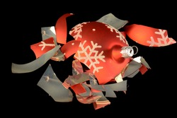 An overhead view of a broken Christmas bauble that has fallen to the floor and shattered into pieces.