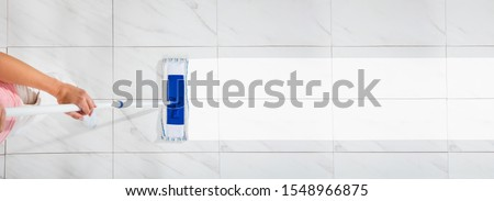 An Overhead View Of A Female Cleaning The White Floor With Wet Mop Stock foto ©