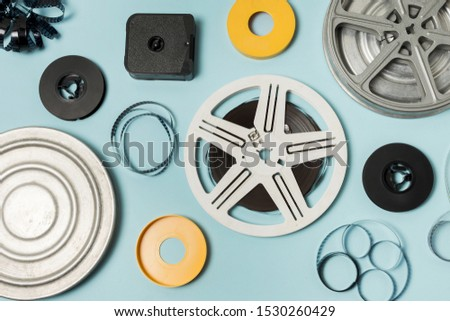 An overhead view of cases; filmstrips and film reels on blue background #1530260429