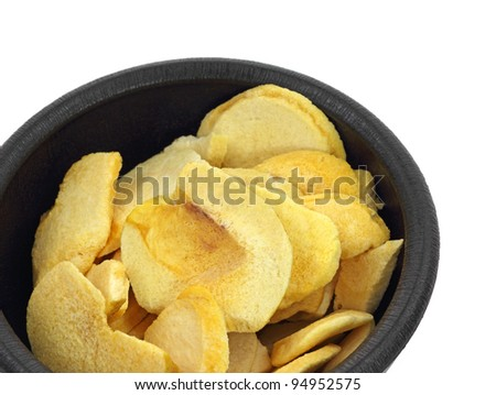 An overhead view of dried peach slices in black bowl.