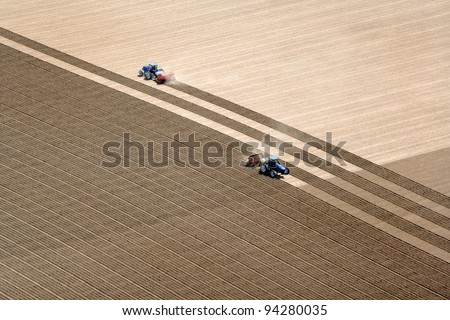An overhead view of farmland being plowed and planted.