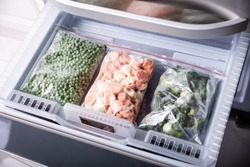An Overhead View Of Frozen Vegetables In Plastic Bag Over Refrigerator Tray