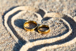 An Overhead View Of Golden Wedding Rings Inside The Heart Shape On Sand At Beach
