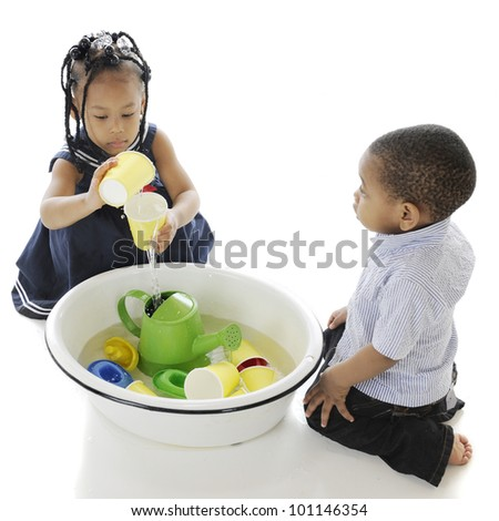 An overhead view of two adorable kids playing with toys in a tub of water.  On a white background.