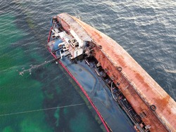 An overturned rusty tanker ran aground. Environmental disaster and oil spill into the sea by the sea. Old ship on the background of the emerald sea.