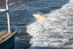 An overturned surf board is seen riding a wave in the ocean with the hand of the surfer who is under the board seen