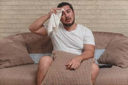 An overweight man wipes the sweat off his forehead with a white towel. Heat wave, broken air conditioner or sweltering temperature indoors.