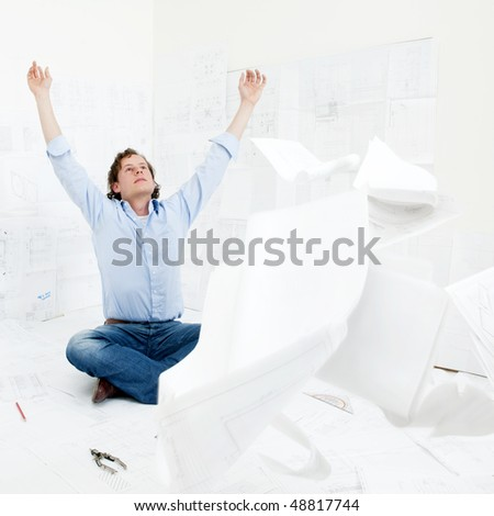 An overworked engineer throwing the technical drawings he's been revising towards the camera, raising his hands and head in the air in despair