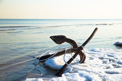An patinous anchor alongside frozen seashore in winter