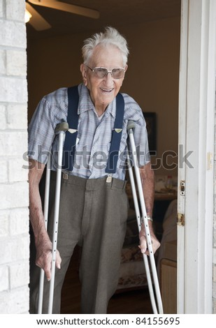 An smiling elderly man standing in the door of his apartment with crutches - stock photo
