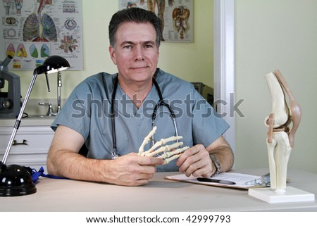 An smiling orthopedic doctor holding a skeletal model of the human hand, with a model of a human knee on his desk.