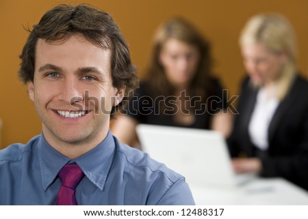 An smiling young male executive in focus in the foreground while his female colleagues work on a laptop behind him
