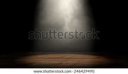 An stage lit by a single spotlight on a dark background