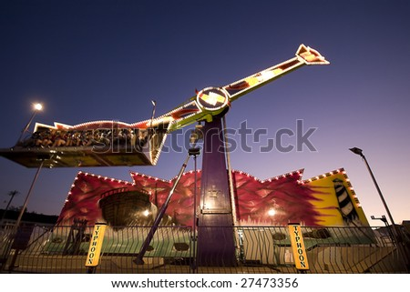 An state fair ride spinning in the dusk