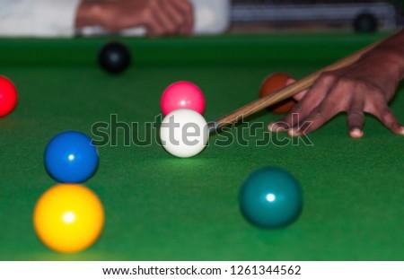 An Tanzanian young boy hitting the snooker ball  #1261344562