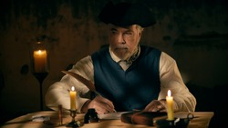 An 18th century scene of a mature man in a tricorn or cocked hat writing a letter using a feather quill pen in a room lit by candlelight and overhead window light.