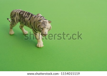 An tiger animal is a children's toy. Plastic figurine for the game. Green background. Farm and the zoo.