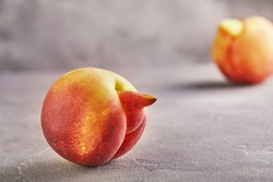 An ugly fruit or vegetable. Strongly ugly peach mutants on a gray background. Ugly fruits are not in high demand.