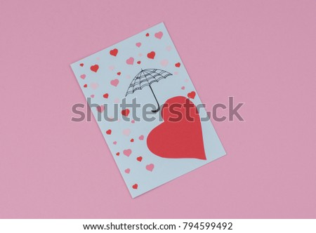 an umbrella that protects from falling hearts on a pink background #794599492