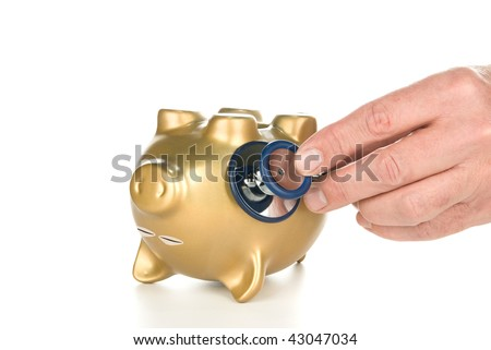 An unconscious piggy bank being examined with a stethoscope for its financial life after a poor economy and recession.