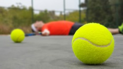 An unfit tennis player lying exhausted on the court ground