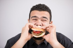 An unfitness man takes a bite of a burger sandwich with closed eyes.