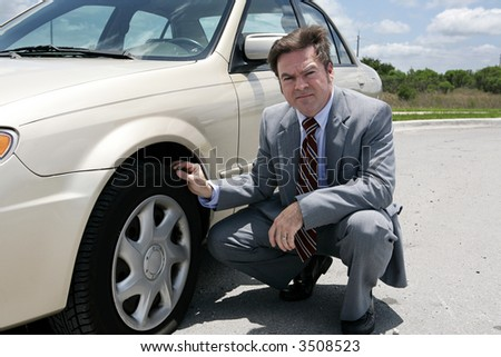 An unhappy looking businessman discovering a screw in his flat tire.