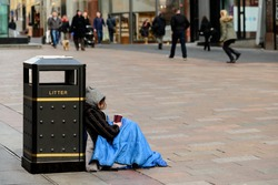 An unidentifed person begging on a street in Glasgow, Scotland.