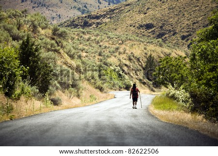 An unidentifiable man walks down a dirt road