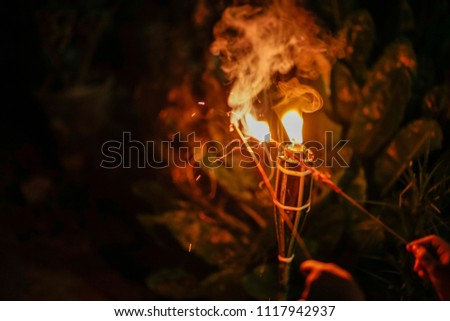 """An unidentified hand holding firework toward malay traditional lamp or """"pelita"""" during Hari Raya celebration. Eidul Fitri concept. image contain grain and soft focus.  #1117942937"""