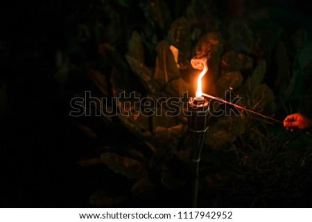 """An unidentified hand holding firework toward malay traditional lamp or """"pelita"""" during Hari Raya celebration. Eidul Fitri concept. image contain grain and soft focus.  #1117942952"""