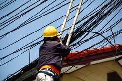 An unidentified male worker on bamboo ladder is repairing telephone line near the community.