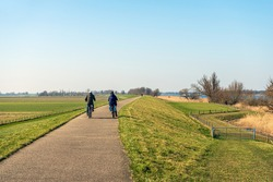 An unidentified man and woman are cycling on a winding Dutch dike near the village of Drimmelen in the province of Noord-Brabant. It's a sunny day at the end of the winter season.