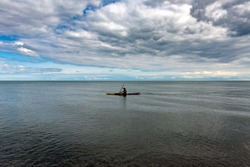 An unidentified person rowing a boat in Lake Ontario with dramatic clouds in the background