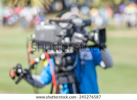 An unidentified sport photographer is working during golf tournament in golf course for live broadcasting.