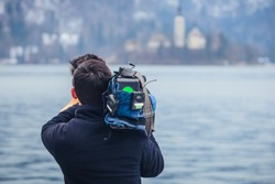 An unknown cameraman is filming a famous lake of Bled, Slovenia in a winter time. Concept of famous and beautiful places being filmed on tape.